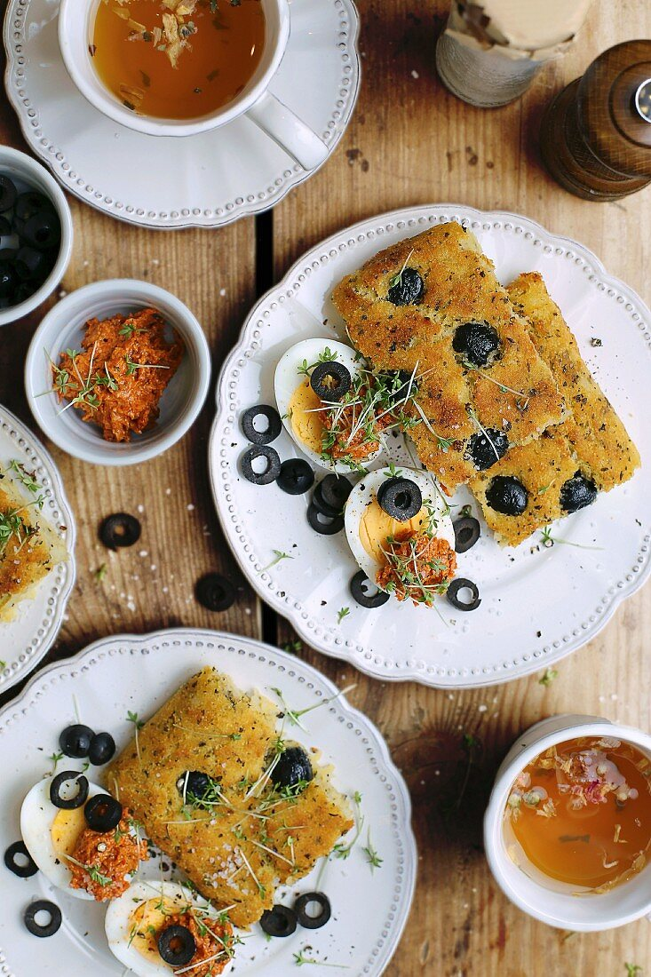 Gluten-free focaccia with black olives on a white plate