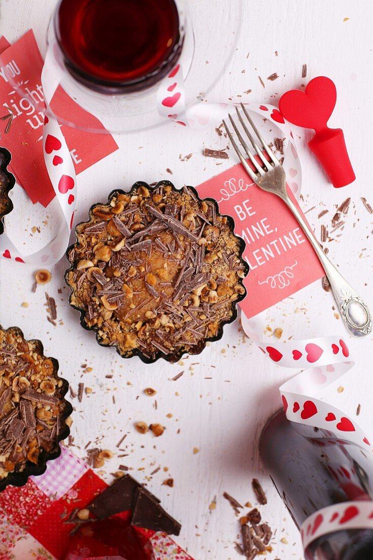 Valentinstags-Dessert mit Rotwein und Deko auf weißem Tisch