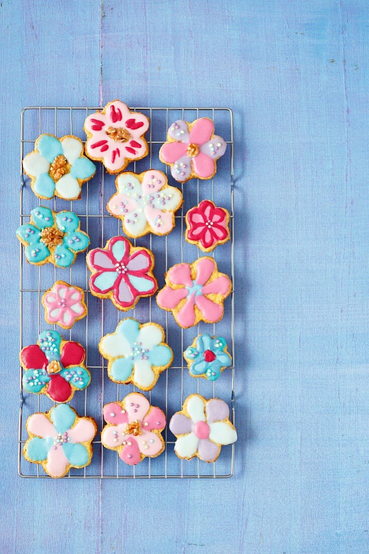 Flower-shaped carrot cookies with colourful sugar glaze