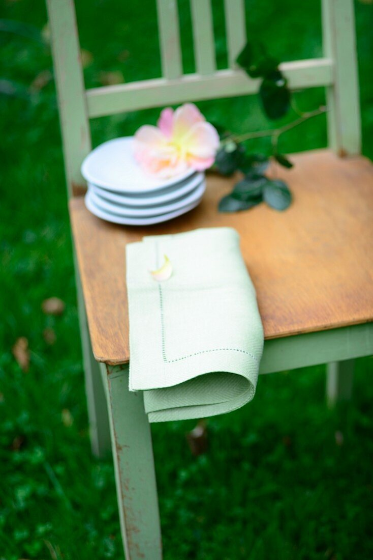 Stack of small plates, cut rose and linen napkin on chair seat