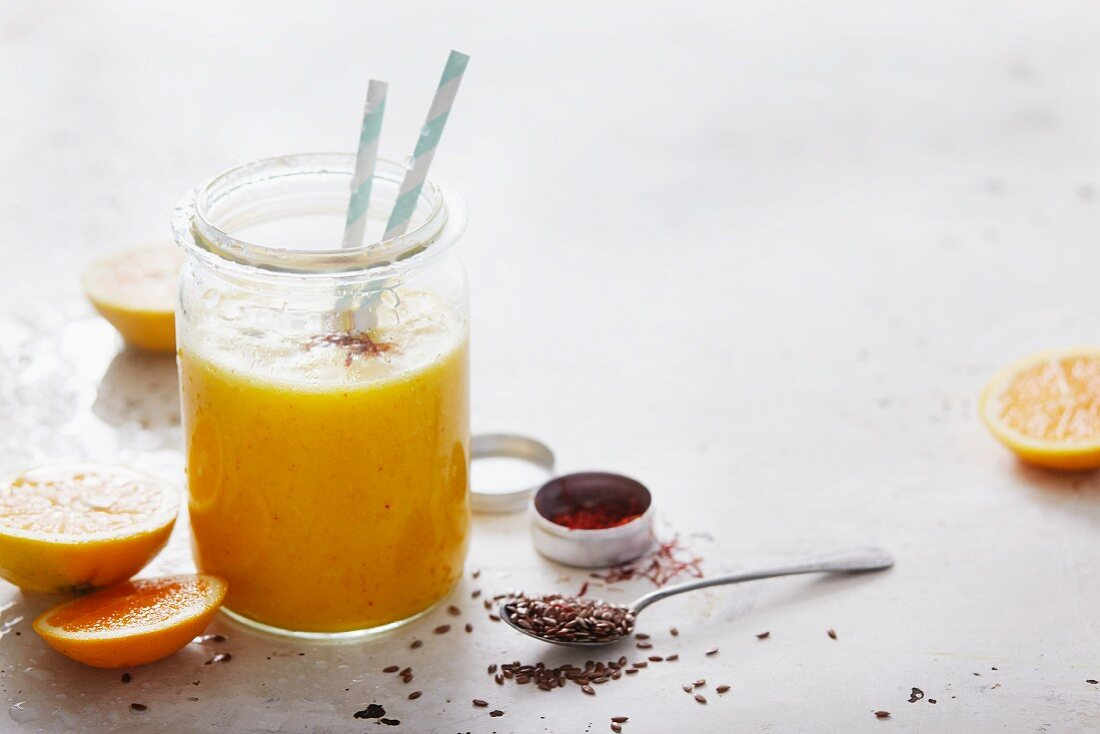 An orange and pineapple smoothie with saffron and flax seeds