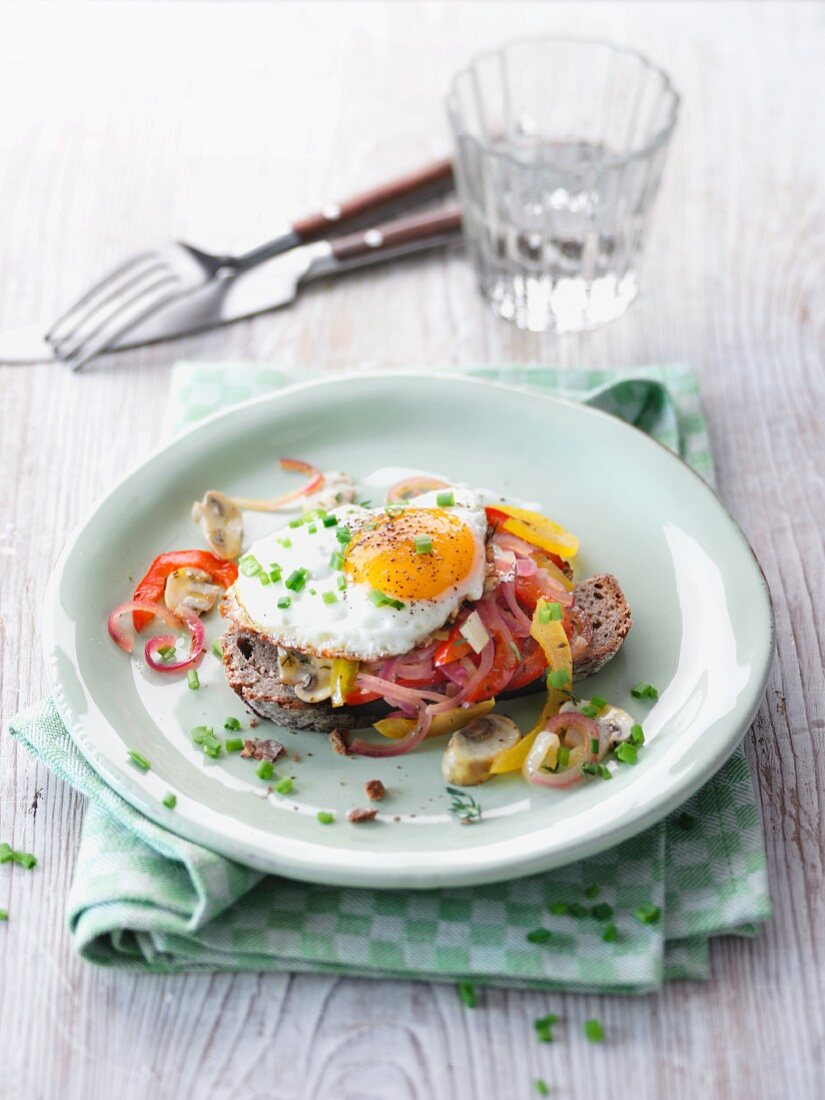 Egg on toast with peppers and onions