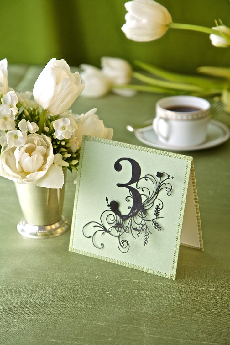 Decorative place card with number 3 on festive table