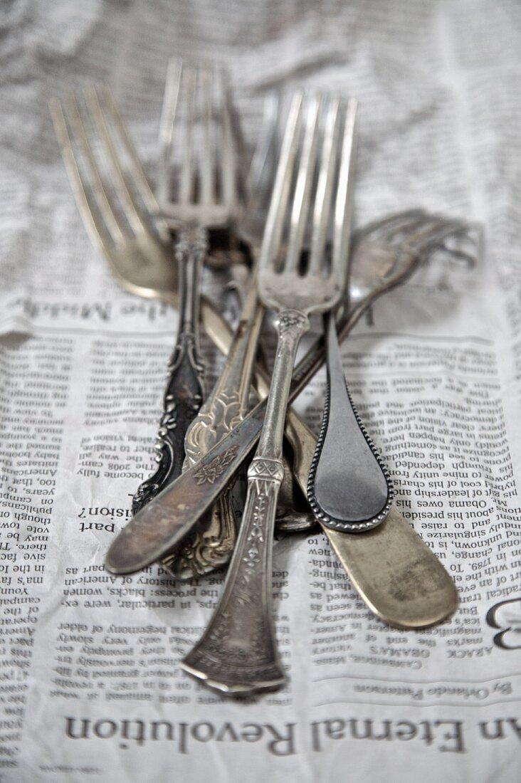 Vintage silver forks on a newspaper