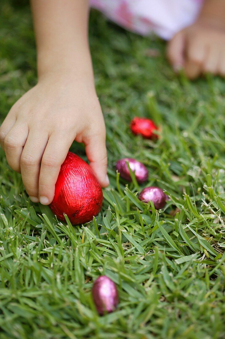 Girl found an Easter chocolate eggs in the garden