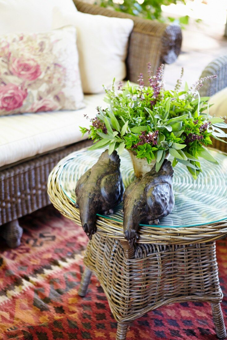 Posy of herbs and hen ornaments on table