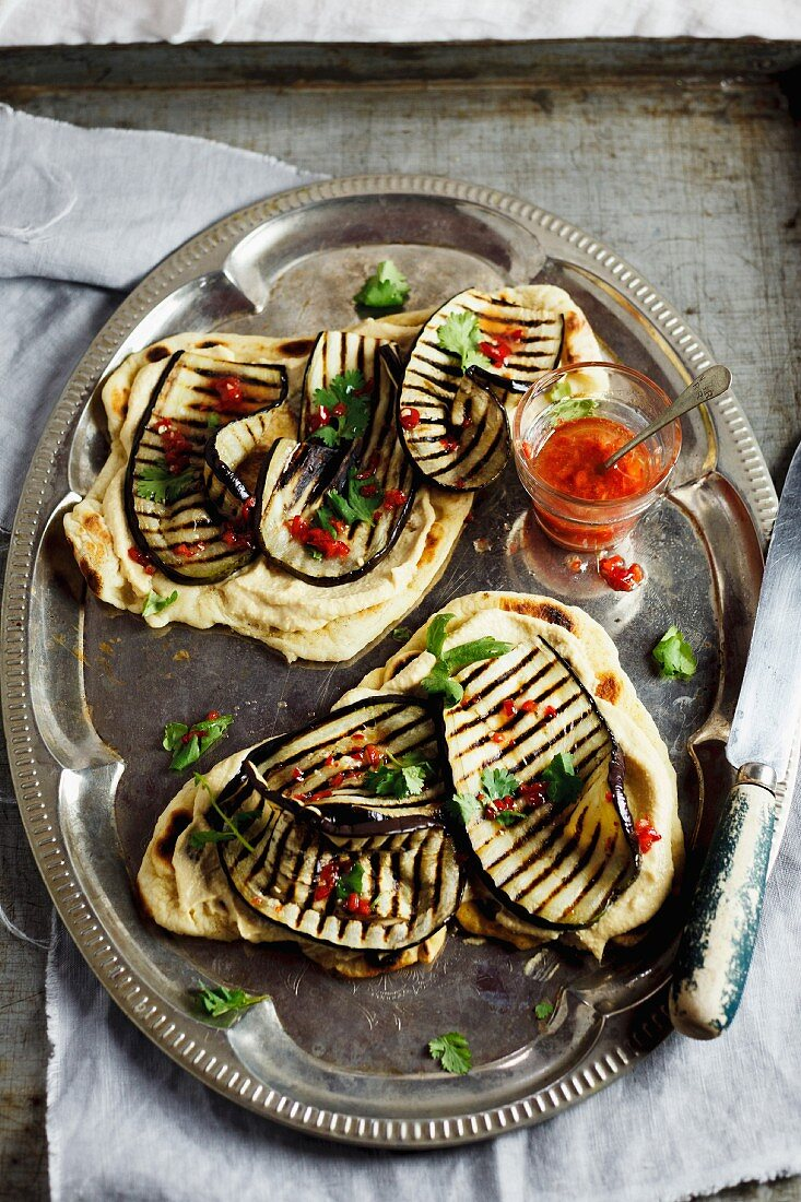 Naan bread with grilled aubergines, hummus and a chilli dressing