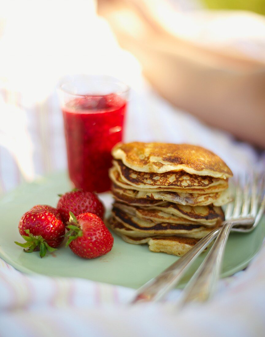 Pancakes with strawberries for breakfast in bed in a field