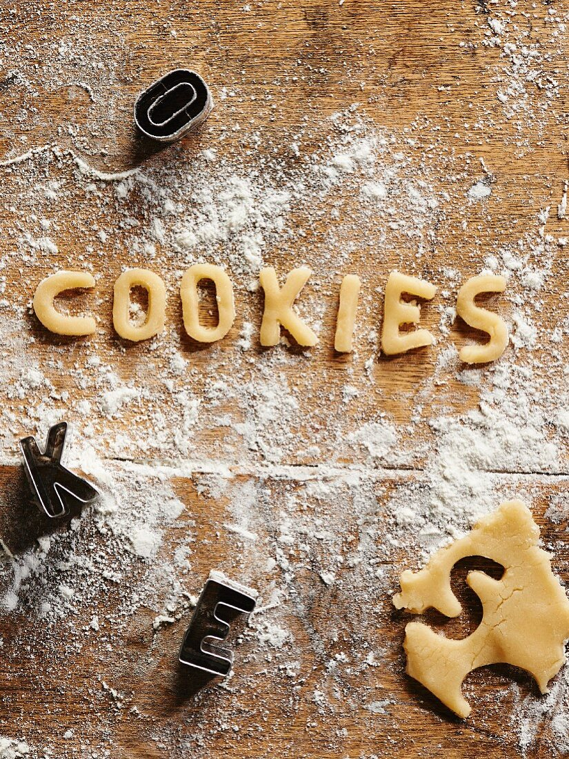Cookie dough, cut-out letters and cutters on a floured wooden surface