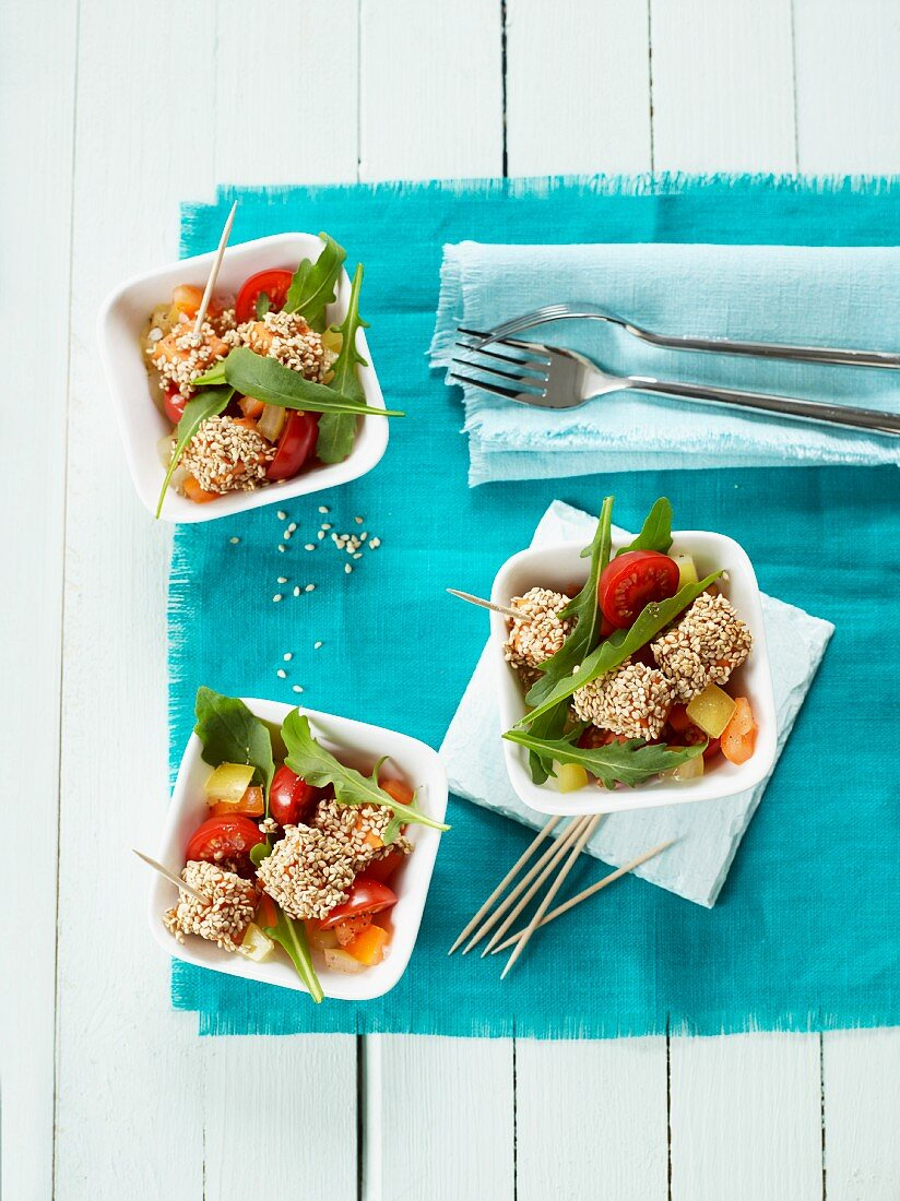 Sweet potato and sesame cubes on a tomato and rocket salad