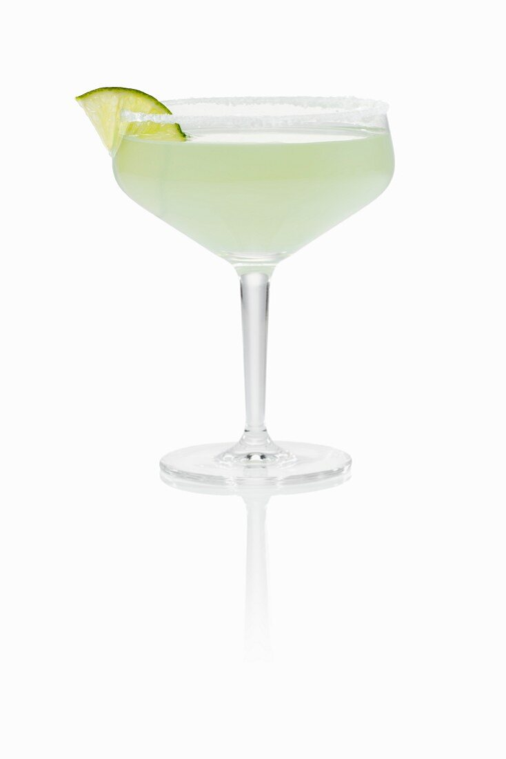 A margarita garnished with lime in a glass with a salted rim