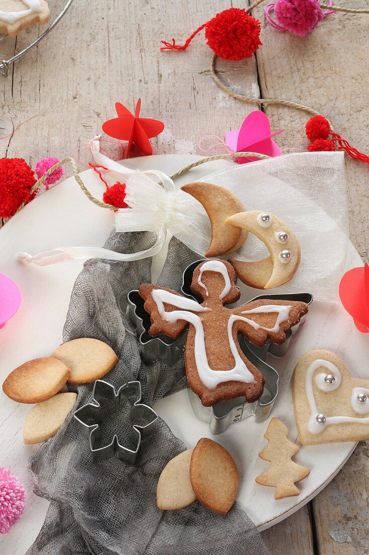 Decorated Christmas biscuits on a plate surrounded by Christmas decorations