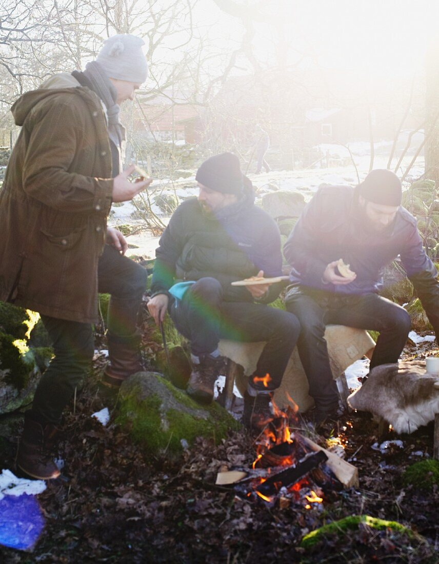 Friends eating pizza around a campfire in winter
