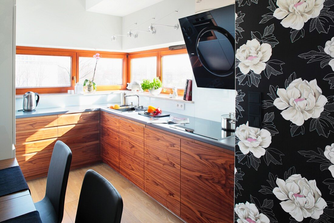 A modern fitted kitchen with wooden cupboards and windows all the way round with a piece of black and white floral wallpaper in the foreground