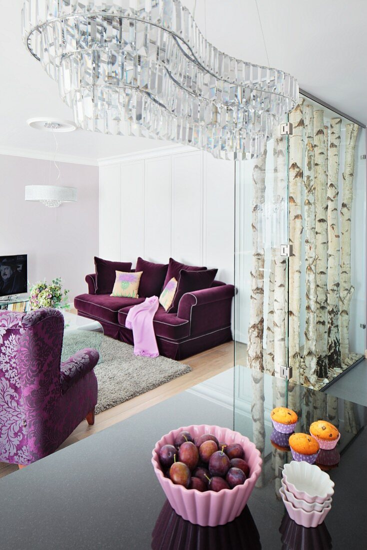 An organically shaped crystal chandelier above a the reflective surface of a kitchen bar with elegant, purple upholstered furniture in the background