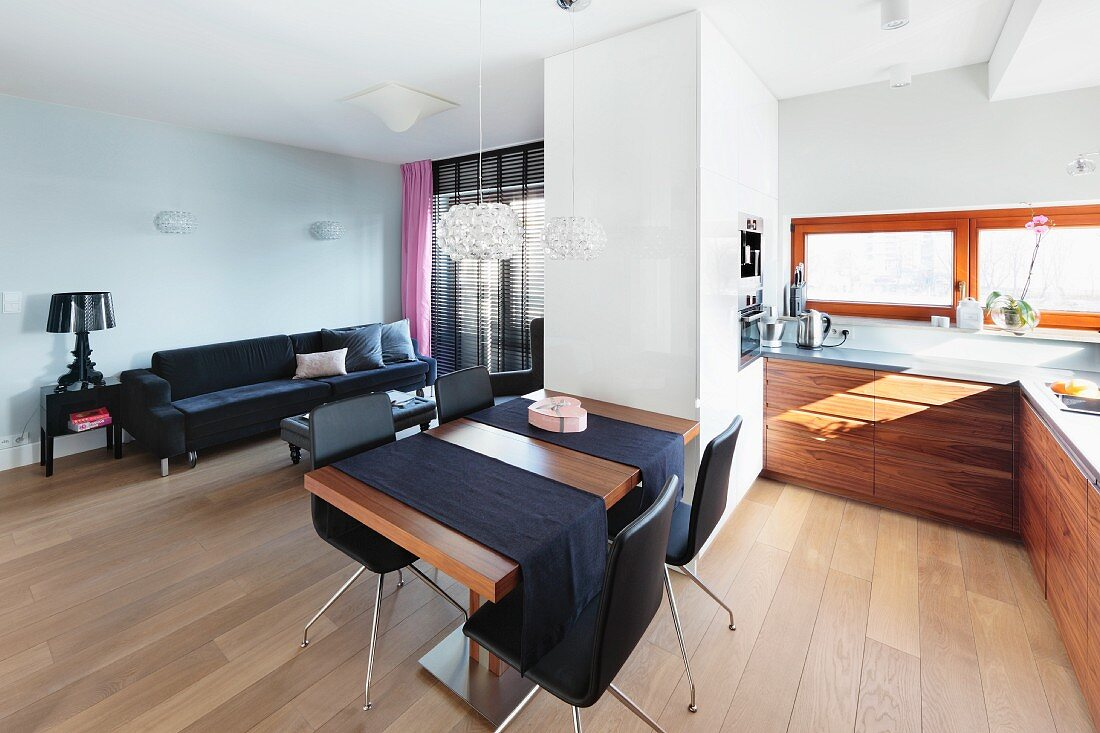 An open plan living area with a white room divider cupboard between the kitchen and living room with a dining table and black chairs in the middle