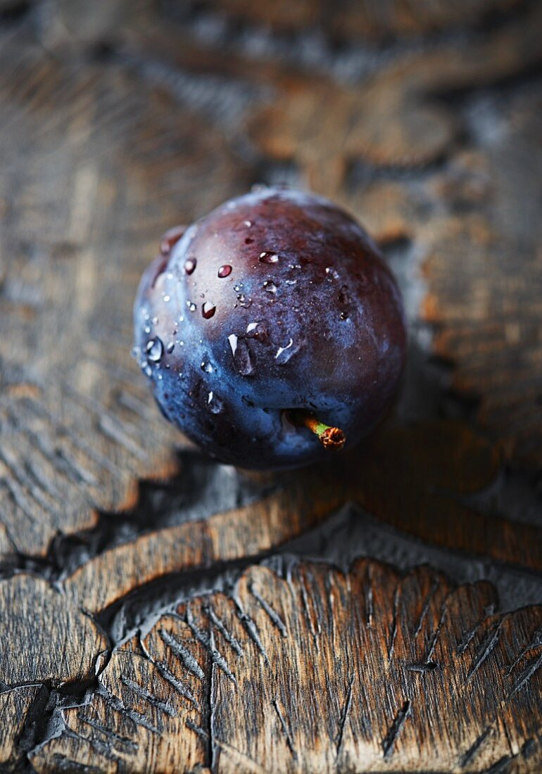 A freshly washed plum on a wooden surface