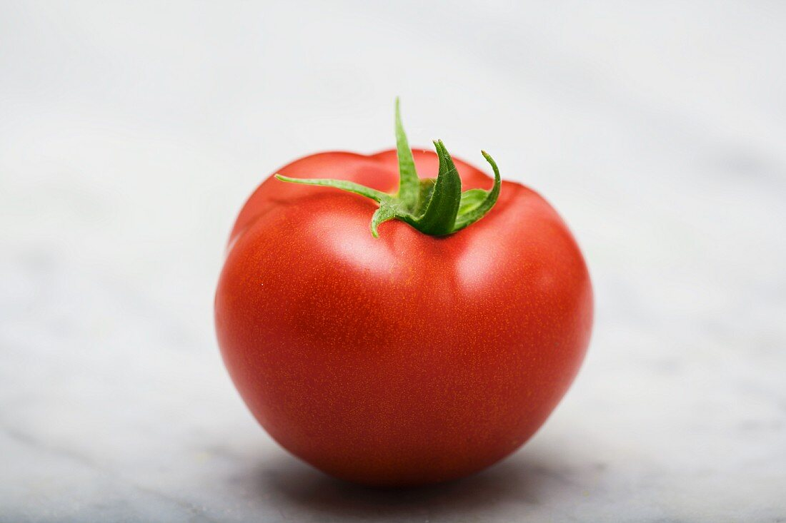 A tomato on a marble surface