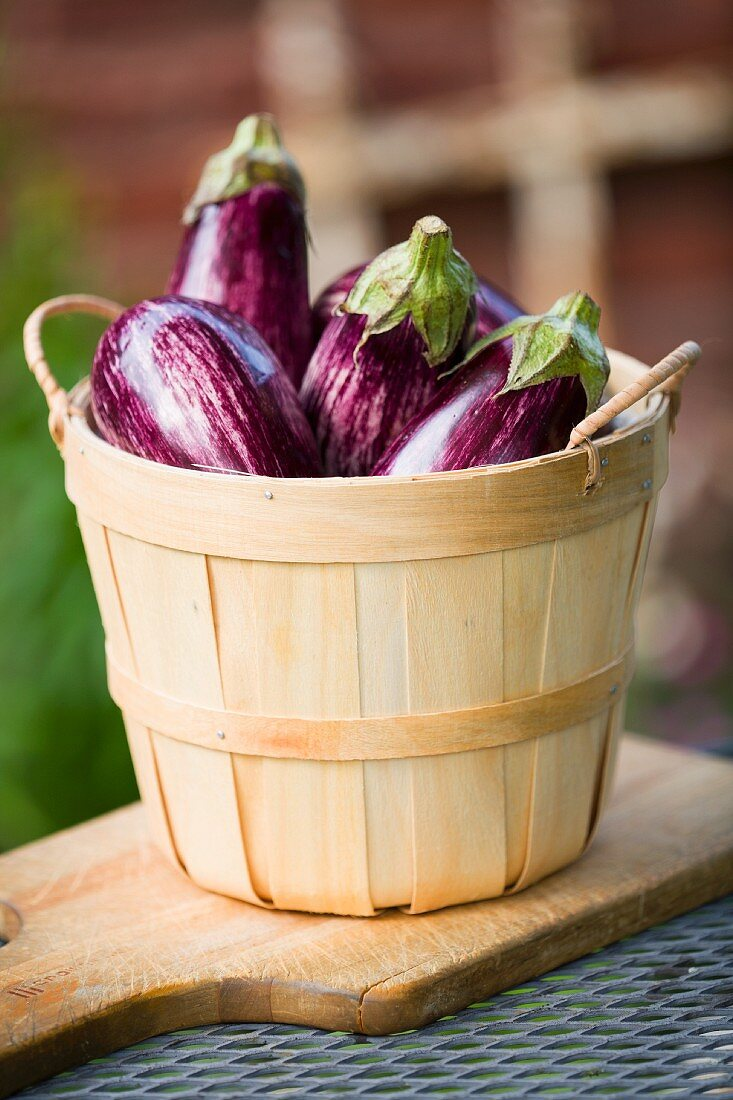 Aubergines in a wooden basket on a chopping board