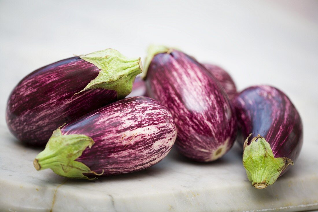 Striped aubergines on a marble surface