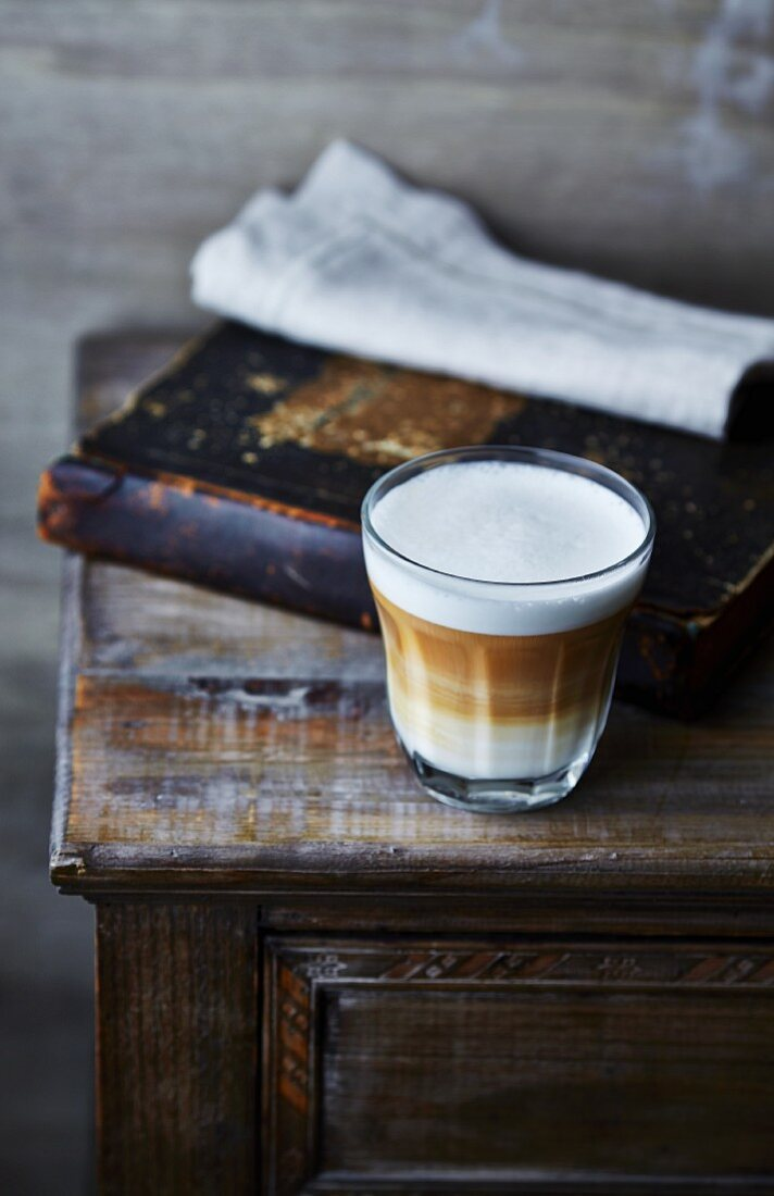 Glass of latte macchiato coffee on old cabinet