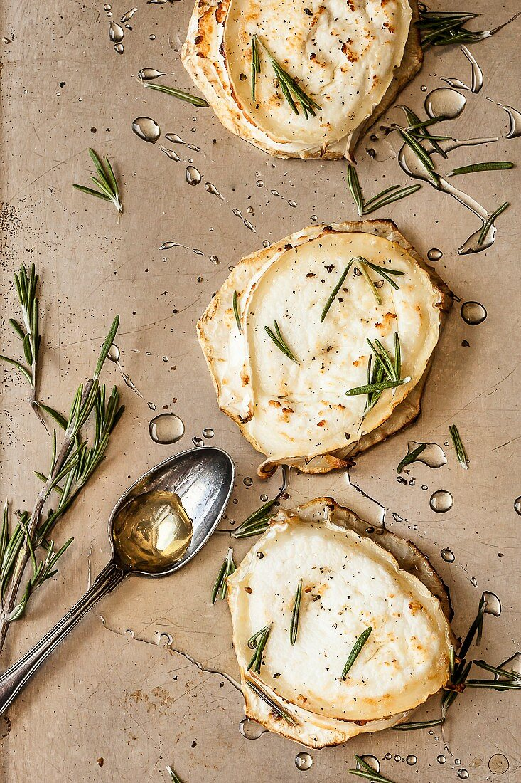 Slices of celeriac topped with melted goat's cheese and garnished with rosemary and acacia honey