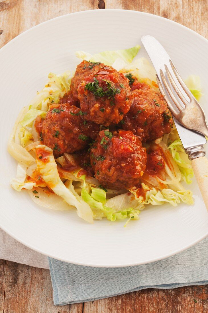 Sweet and sour chicken meatballs with chilli sauce on a bed of salad