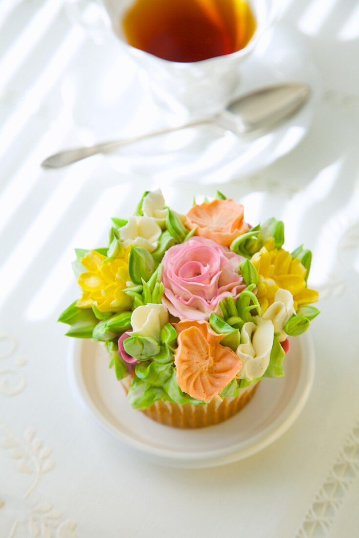 A cupcake with romantic sugar flowers in front of a cup of tea