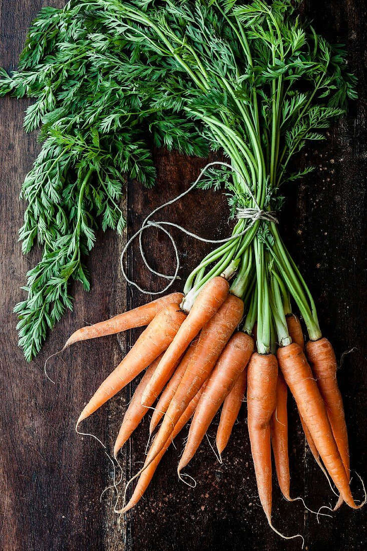 A bunch of carrots on a wooden surface