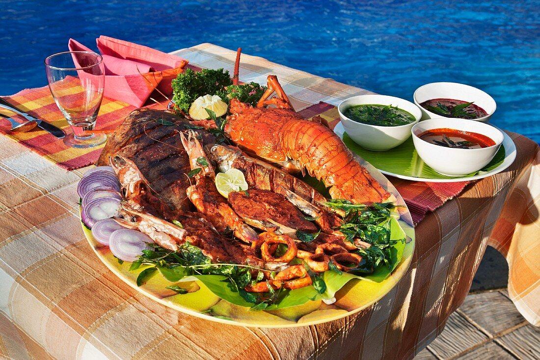 Würzige Fischplatte mit Hummer und verschiedenen Saucen (Indien)