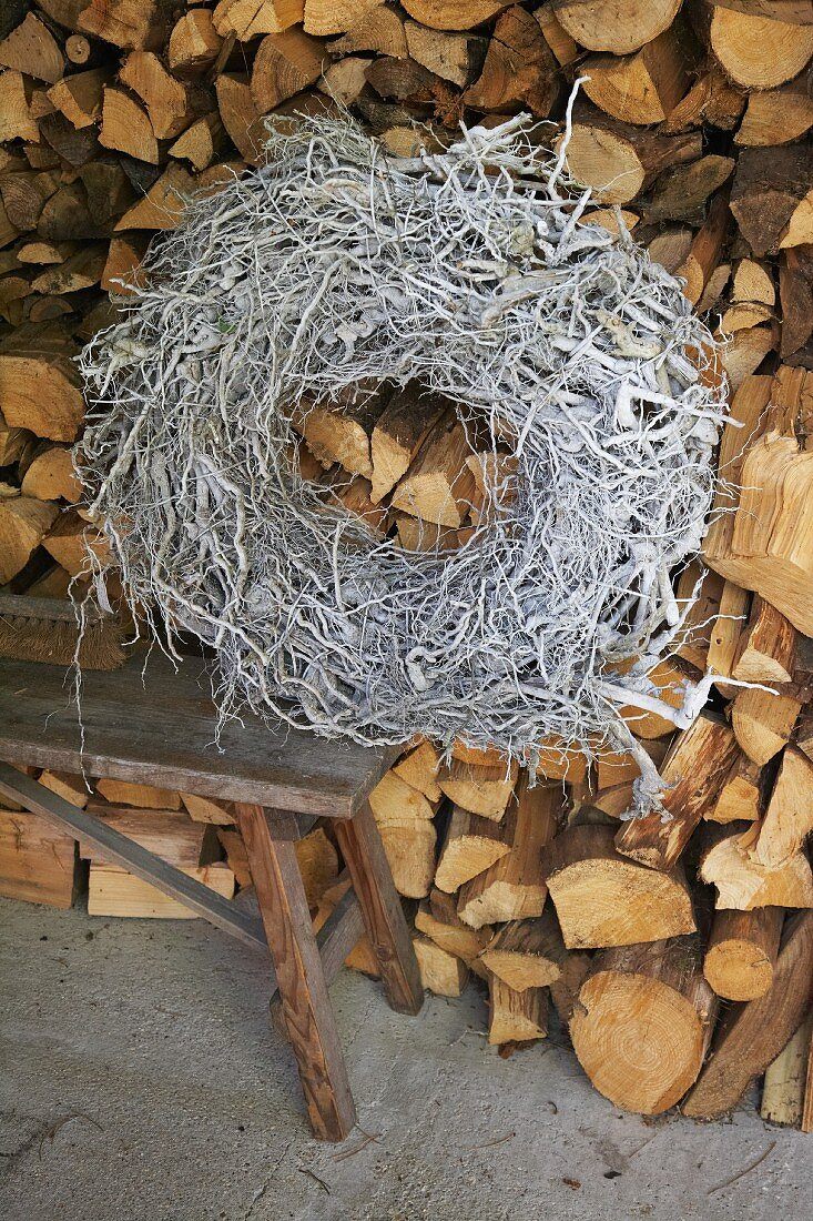 A woven wreath on a bench against a wood pile