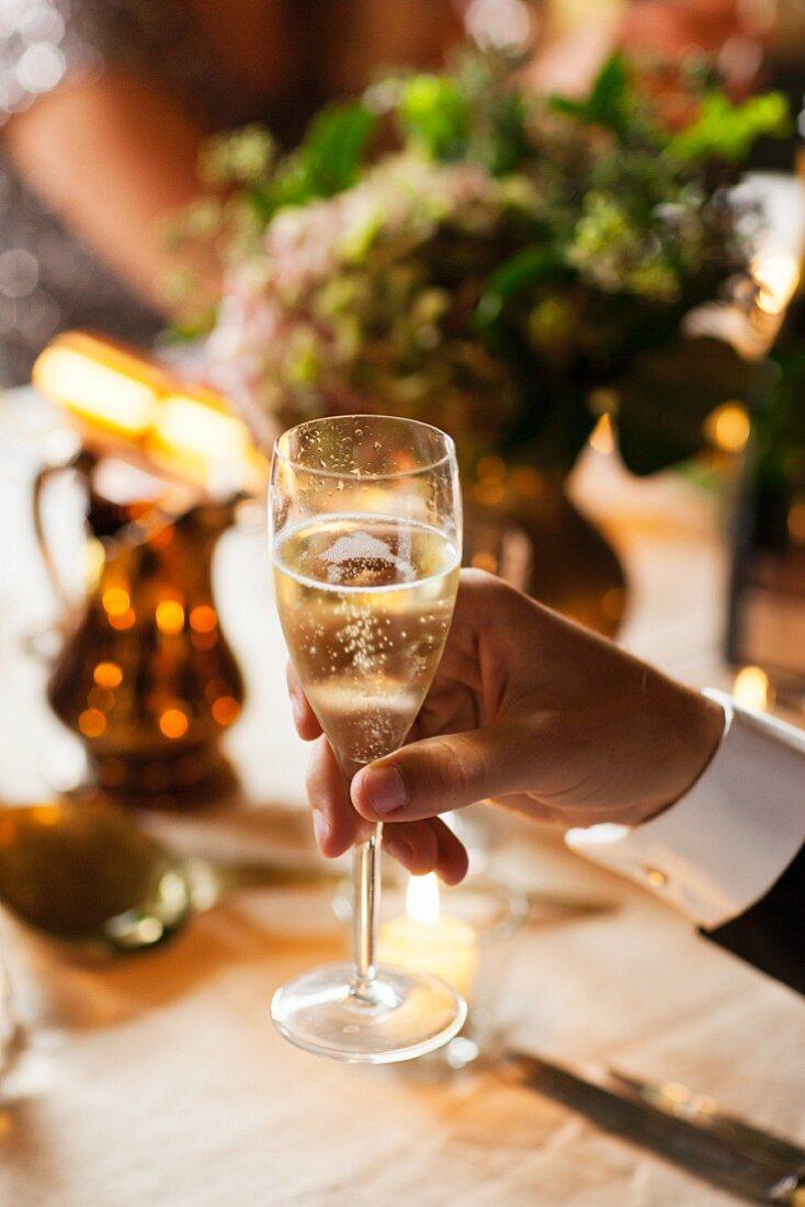 Hand hält ein Glas Champagner