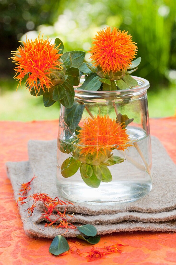 Three safflowers in a glass of water as a centrepiece on a garden table