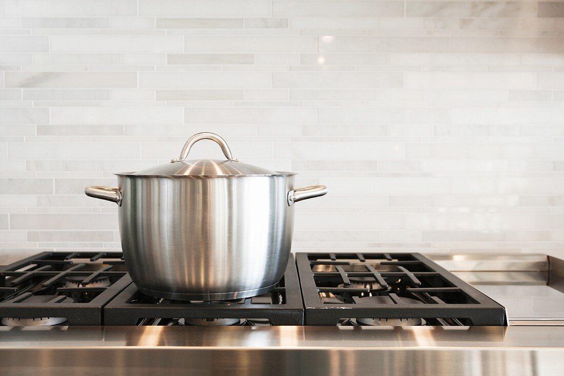 Saucepan on hob with splashback in kitchen