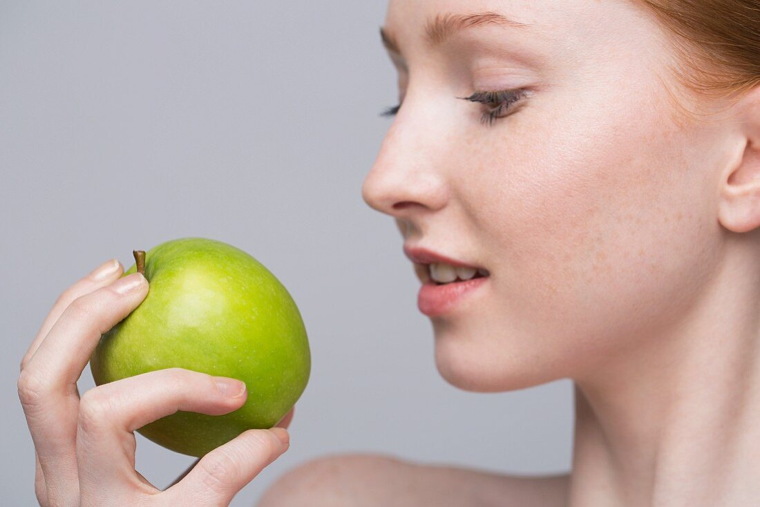 A portrait of a young woman holding a green apple