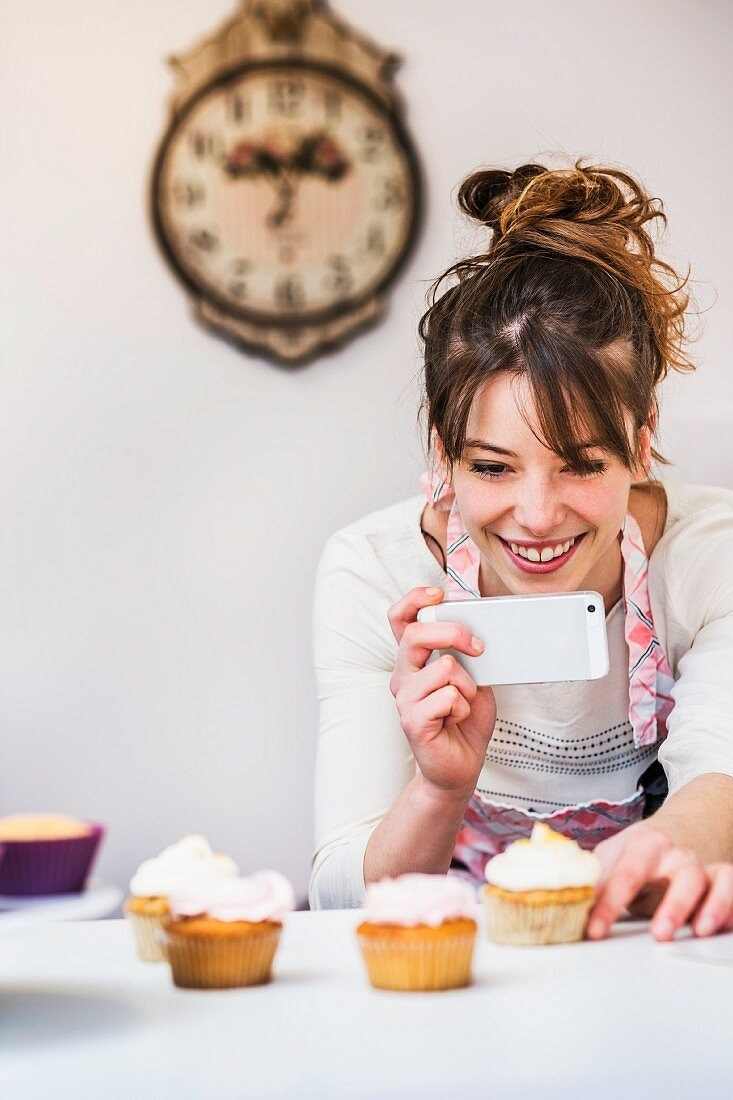 A woman in a kitchen taking a photo of cupcakes with her smartphone