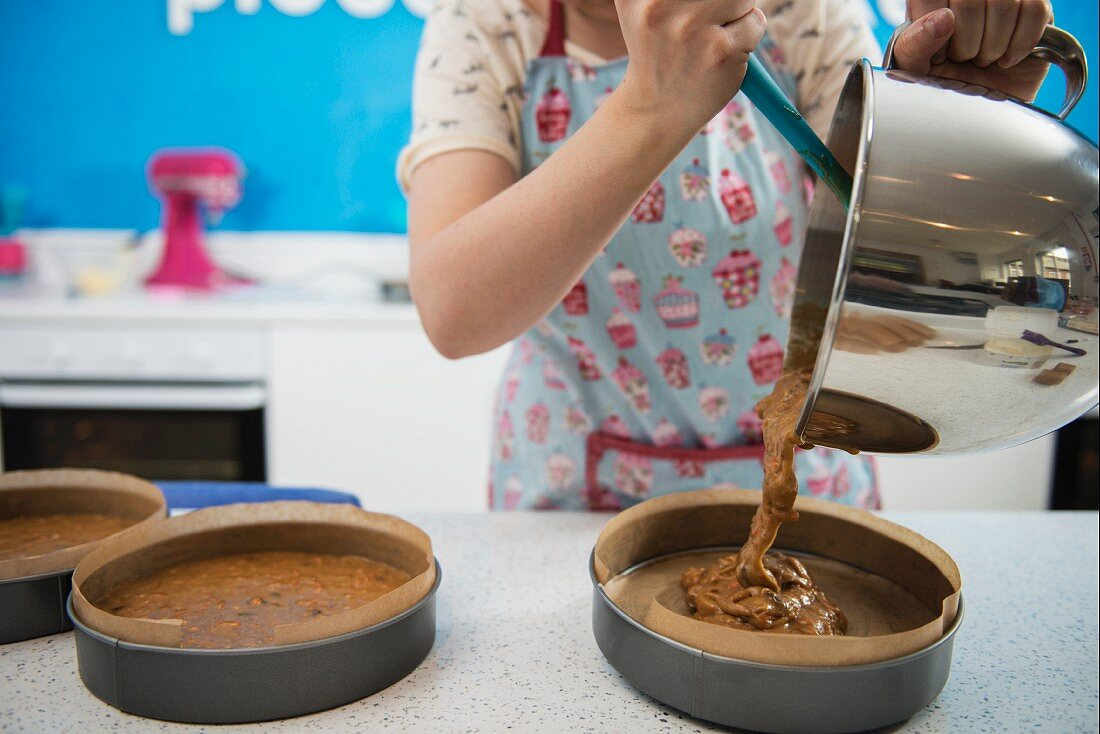A woman pouring cake mixture into cake tins in a bakery