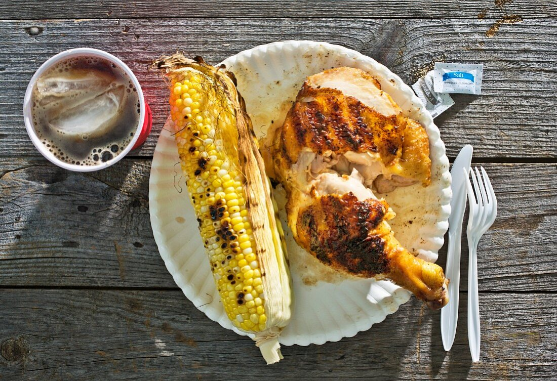 A spicy grilled chicken leg served with corn on the cob