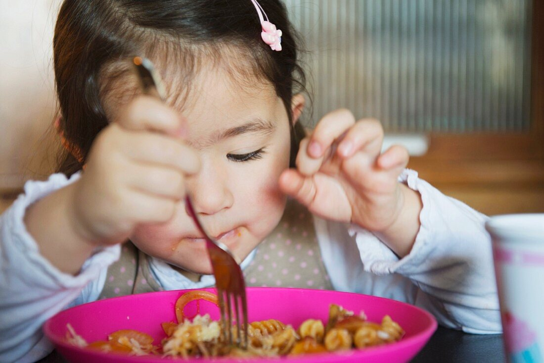 A little girl eating pasta with a fork