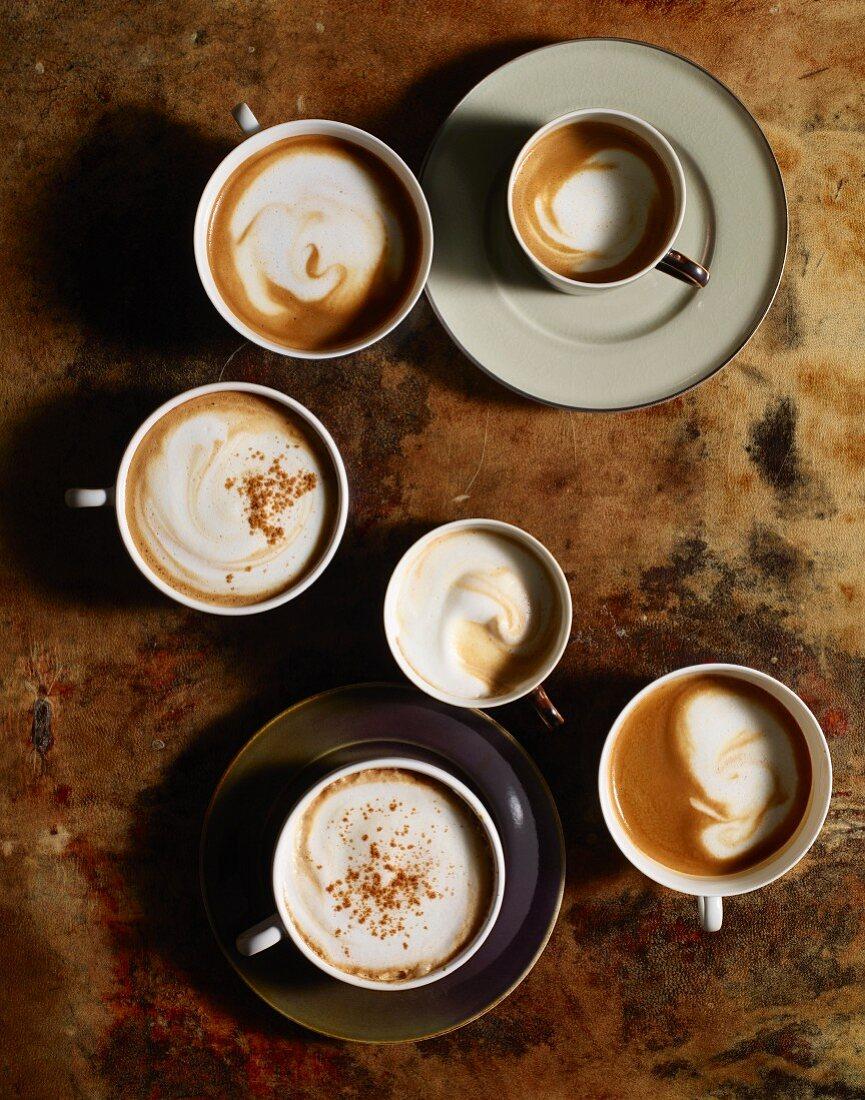 Mehrere Tassen Kaffee mit aufgeschäumter Milch und Zimt