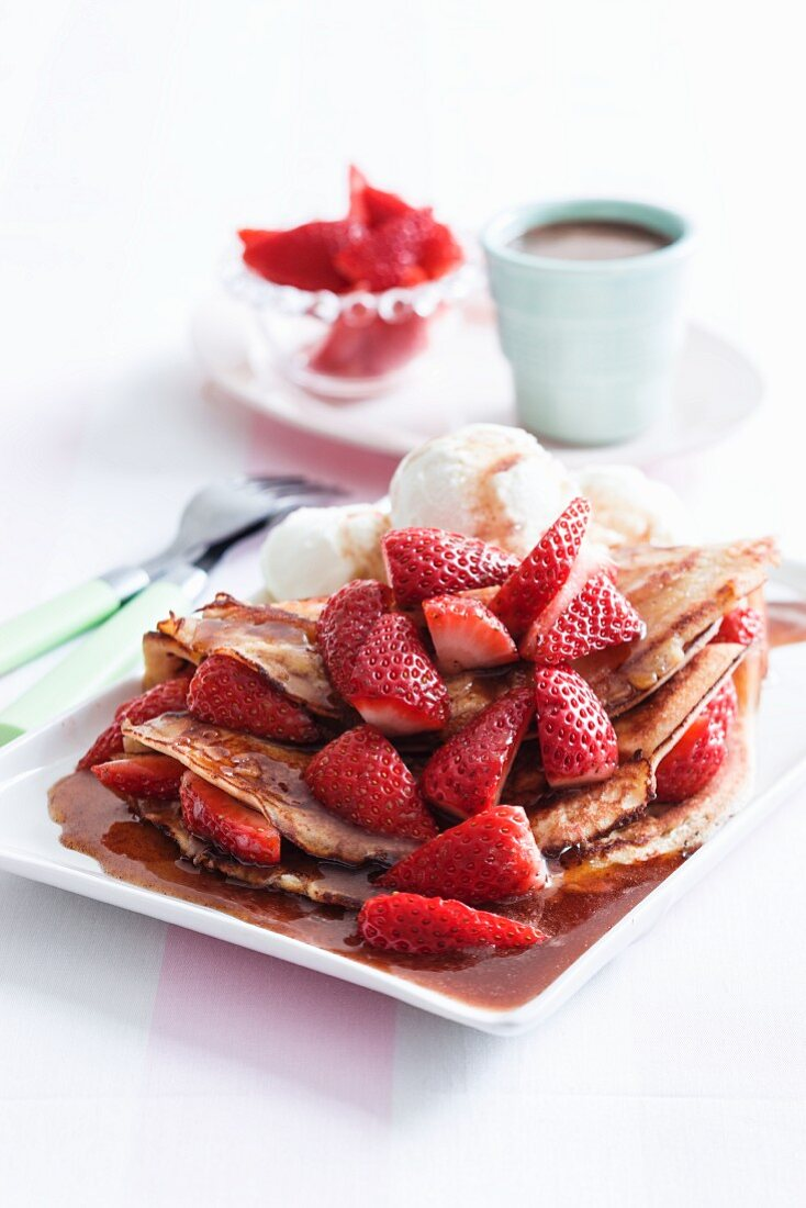 Pancakes with maple syrup, ice cream and strawberries