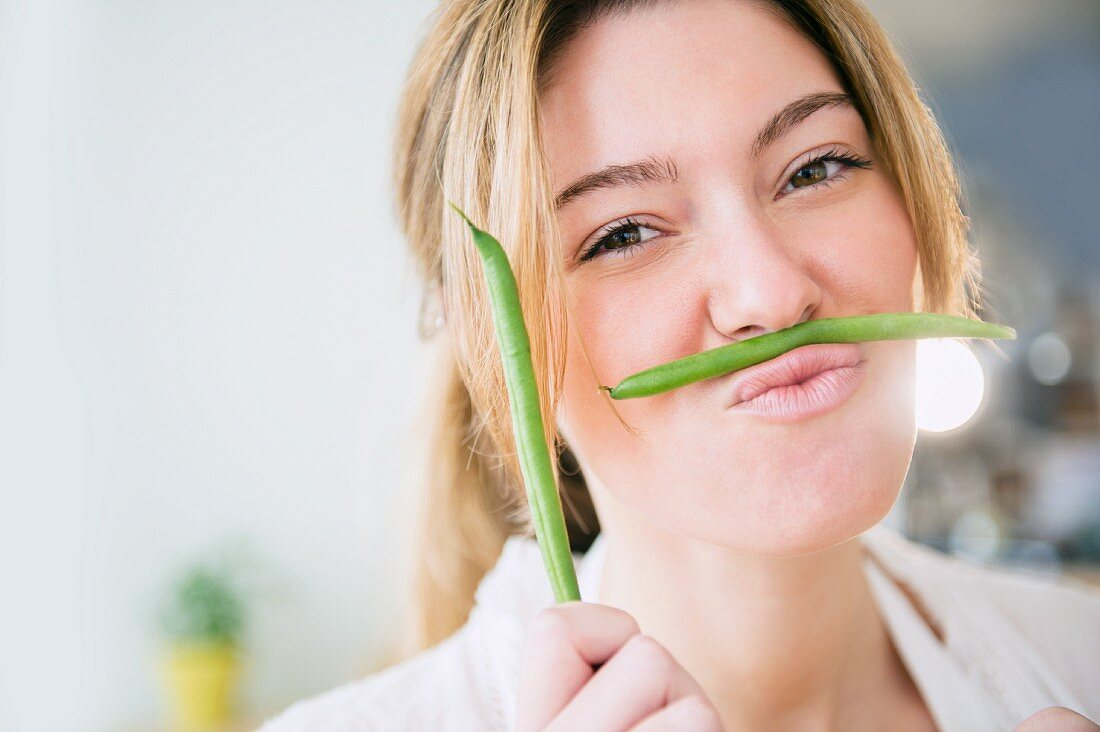 A young woman holding a green bean