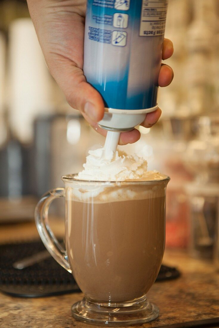 A waiter squirting whipped cream onto cup of hot chocolate