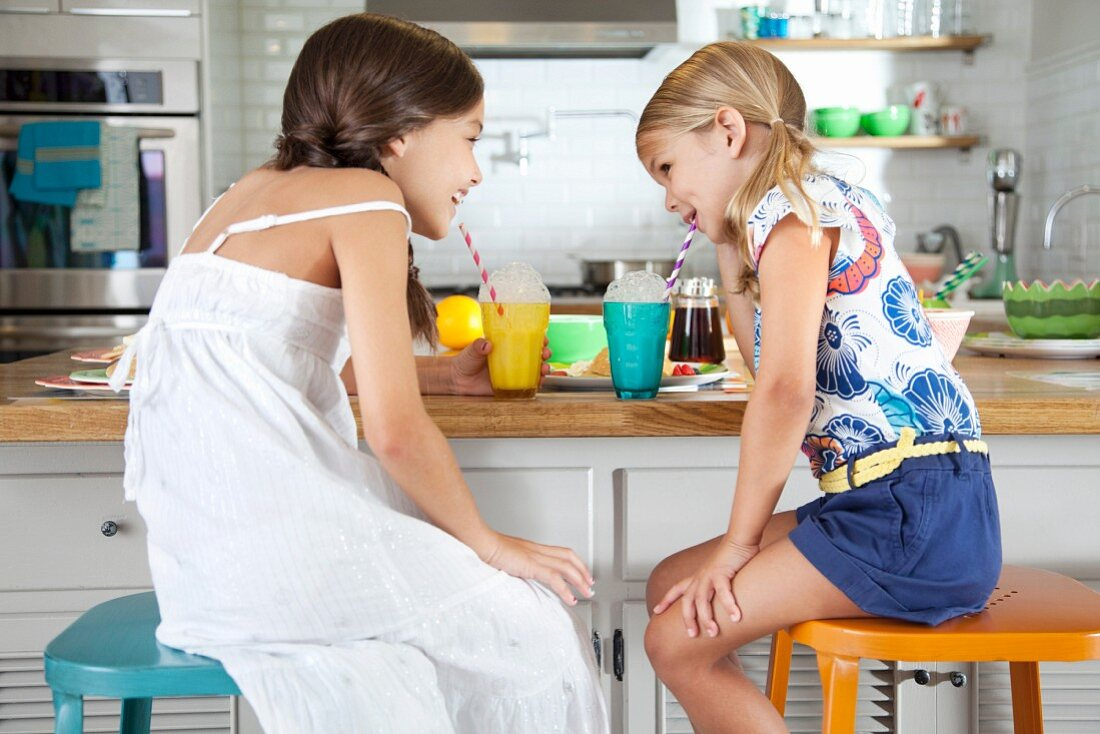 Two sisters in a kitchen blowing bubbles into drinks through straws
