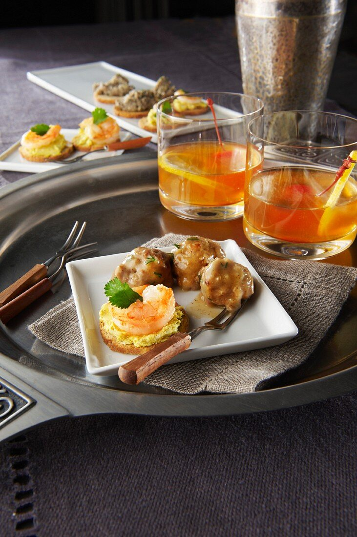 Two aperitif glasses and canapés on a tray
