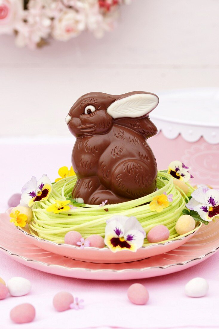 A chocolate Easter bunny in a nest decorated with flowers and chocolate eggs