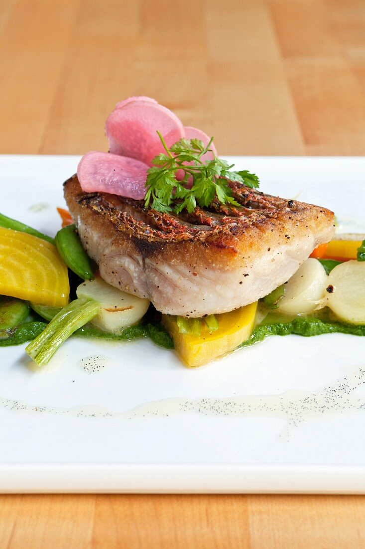 Fried snapper on a bed of spring vegetables with water cress and pickled radishes
