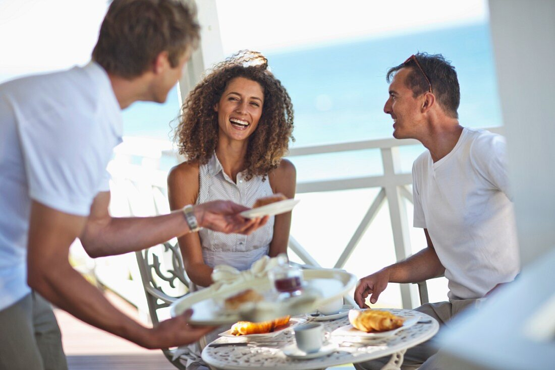 A couple having breakfast on the balcony of a beach-side hotel