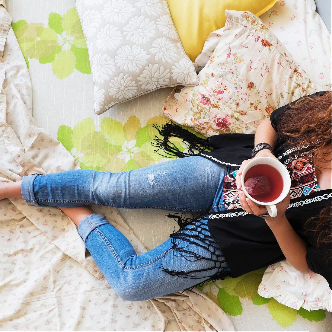 A woman lying on a bed with a cup of tea
