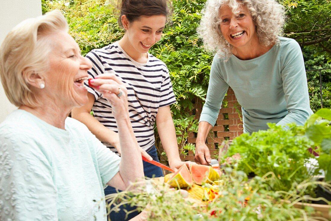 Three women preparing food at a garden table